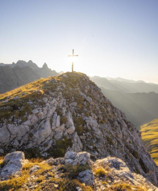 Das Gipfelkreuz des Muttlerkopfs in der Abendsonne